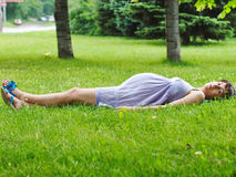 Беременная женщина лежа на траве Стоковое фото RF