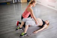 Беременная женщина лежа на тренировке циновки спортзала с тренером Стоковое фото RF