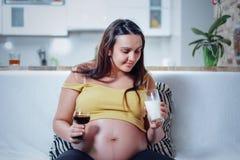 Беременная женщина держа вино и молоко стоковая фотография rf