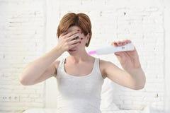 Беременная женщина держа розовый положительный тест на беременность покрывая ее глаза с ее рукой стоковые изображения rf