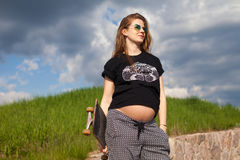 Беременная женщина держа скейтборд Стоковое Фото