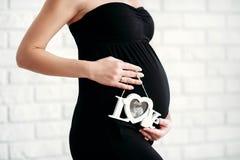 Беременная женщина держит развертку ультразвука на ее животе Стоковое фото RF