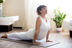 Беременная женщина делая верхнюю йогу собаки облицовки представляет дома стоковая фотография
