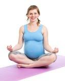 Беременная женщина делая йогу в студии стоковое фото rf