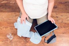Беременная женщина делая онлайн покупки на таблетке для предпологаемого ба Стоковая Фотография
