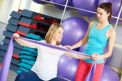 Беременная женщина делая тренировку фитнеса с тренером Стоковое Изображение RF