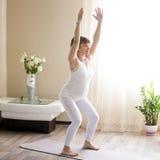 Беременная женщина делая Utkatasana, йогу стула представляет дома стоковая фотография rf