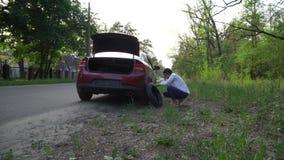 Беременная женщина изменяя прокалыванную автошину на автомобиле ремонт автомобилей на дороге акции видеоматериалы