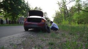 Беременная женщина изменяя прокалыванную автошину на автомобиле ремонт автомобилей на дороге видеоматериал