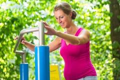 Беременная женщина имея разминку фитнеса на взбираясь рамке Стоковое Изображение