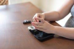Беременная женщина используя метр глюкозы для того чтобы проверить уровень сахара в крови стоковые изображения