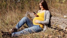 Беременная женщина использует ее smartphone сидя в парке видеоматериал