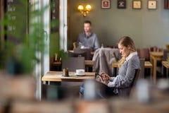 Беременная женщина используя таблетку цифров на кафе стоковое фото rf