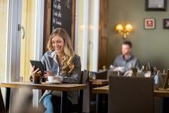 Беременная женщина используя таблицу цифров в кафе Стоковые Изображения RF