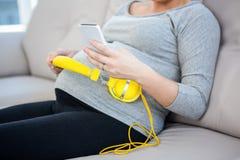 Беременная женщина используя smartphone Стоковое Изображение