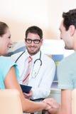 Беременная женщина и ее партнер видя врача стоковые фотографии rf