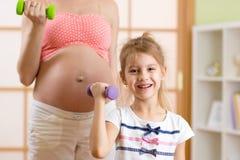 Беременная женщина и ее старший ребенок делая фитнес Стоковые Изображения RF