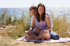 Беременная женщина и ее супруг сидя на beac Стоковые Фото