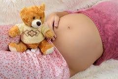 Беременная женщина и игрушка Стоковая Фотография