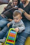 Беременная женщина и супруг смотря таблетку пока сын играет Стоковые Изображения RF