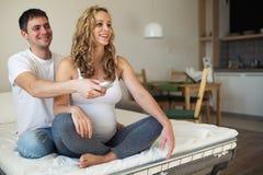 Беременная женщина и супруг смотря ТВ стоковая фотография