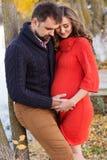 Беременная женщина и человек отдыхают около озера Стоковые Изображения