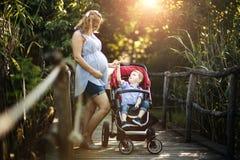 Беременная женщина идя с ребенком в природе стоковые изображения
