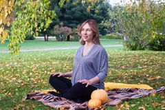 Беременная женщина йоги с шотландкой и портрет тыкв в осени паркуют на траве, дышать, протягивая, статика внешний, лес стоковые изображения