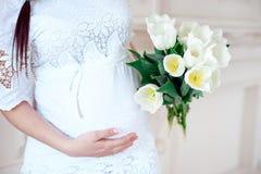 Беременная женщина конца-вверх в белой комнате Стоковые Изображения