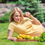 Беременная женщина лежит на траве и ест свежие фрукты Стоковая Фотография RF