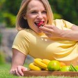 Беременная женщина лежит на траве и ест свежие фрукты Стоковое Изображение