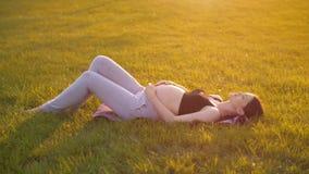Беременная женщина лежит на траве сток-видео