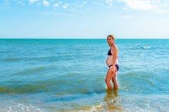 Беременная женщина на море и дышает воздухом и наслаждается миром стоковое изображение rf
