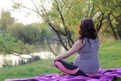 Беременная женщина на озере делает йогу стоковая фотография