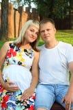 Беременная женщина на стенде и молодой человек представляют в gree лета Стоковые Изображения RF