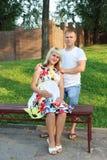 Беременная женщина на стенде и человек представляют в парке зеленого цвета лета Стоковые Фото