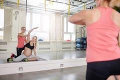 Беременная женщина на тренировке спортзала с личным тренером Стоковая Фотография