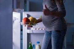 Беременная женщина около холодильника ища еда и закуски на ноче стоковая фотография rf