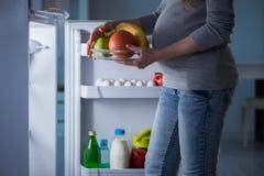 Беременная женщина около холодильника ища еда и закуски на ноче стоковое изображение rf