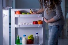 Беременная женщина около холодильника ища еда и закуски на ноче стоковая фотография