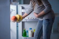 Беременная женщина около холодильника ища еда и закуски на ноче Стоковое фото RF