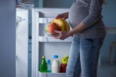 Беременная женщина около холодильника ища еда и закуски на ноче стоковые фотографии rf