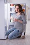 Беременная женщина около холодильника ища еда и закуски стоковая фотография