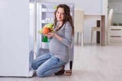 Беременная женщина около холодильника ища еда и закуски стоковая фотография rf