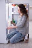Беременная женщина около холодильника ища еда и закуски стоковые изображения rf