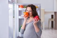 Беременная женщина около холодильника ища еда и закуски стоковое фото rf