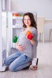 Беременная женщина около холодильника ища еда и закуски стоковые фото