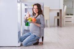 Беременная женщина около холодильника ища еда и закуски Стоковые Изображения