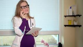 Беременная женщина доктора при улыбка телефона и планшета смотря камеру видеоматериал