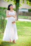 Беременная женщина ослабляя в парке Стоковое Изображение RF